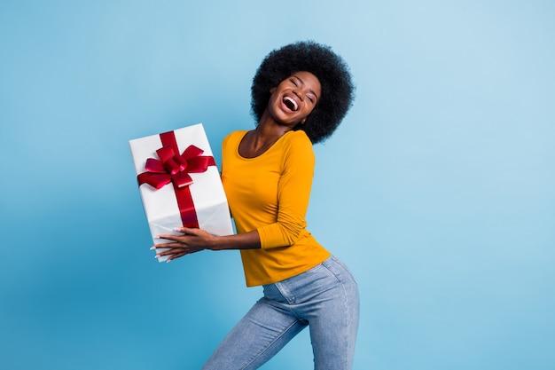 Фото портрет счастливой улыбающейся чернокожей женщины, держащей завернутый подарок, смеясь, танцую, изолированную на ярко-синем цветном фоне