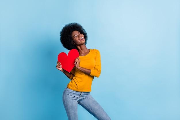 Фото портрет счастливой женщины, держащей открытку с большим красным сердцем двумя руками, изолированными на пастельно-синем фоне