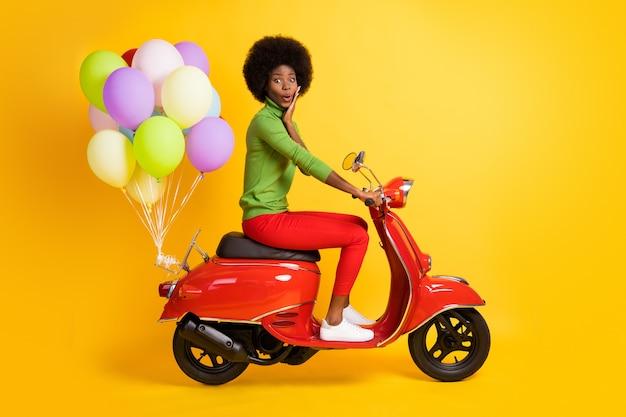 선명한 노란색 배경에 격리된 여러 가지 빛깔의 공기 풍선이 달린 빨간 자전거에 녹색 풀오버를 입은 감명 깊은 갈색 피부 소녀의 사진 초상화