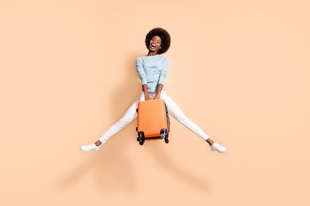 파스텔 베이지색 배경에 격리된 다리를 벌리고 위로 점프하는 주황색 가방을 들고 기뻐하는 아프리카계 미국인 여성의 사진 초상화