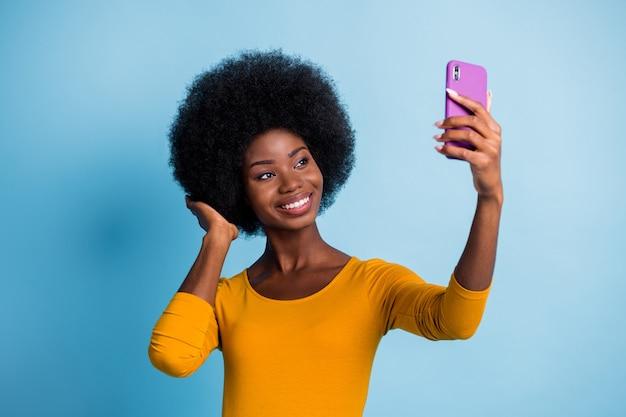 鮮やかな青い色の背景に分離された髪型に触れて笑顔でselfieを取っているかなり黒い肌の女の子の写真の肖像画