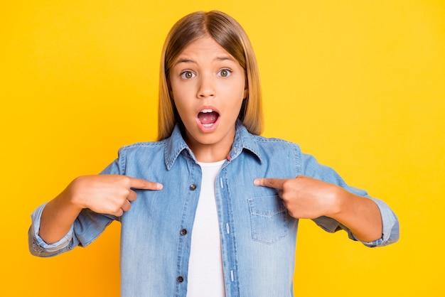 밝은 노란색 배경에 격리된 데님 셔츠를 입고 놀란 자신을 가리키며 슬픈 화가 난 여학생의 사진 초상화