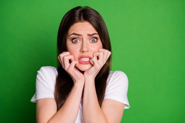 鮮やかな緑色の背景で隔離の両手で顔に触れる怖い女の子の写真の肖像画
