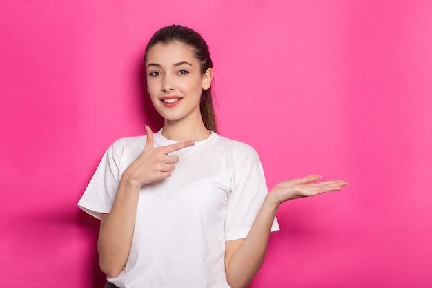 Фото портрет школьницы, указывающей пальцем на ваш продукт, пустое пространство, держащая руку ладонью, в верхней клетчатой рубашке, изолированной на розовом фоне
