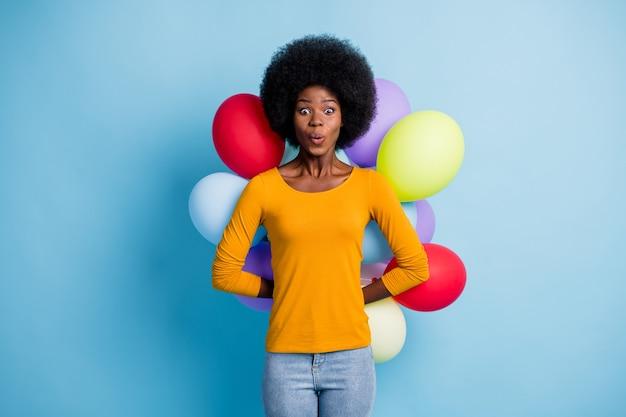 Фотопортрет удивленной темнокожей девушки, прячущей за спиной разноцветные воздушные шары, изолирован на ярком синем фоне