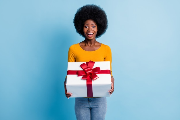 Фотопортрет удивленной улыбающейся чернокожей женщины, держащей обернутую подарком красной лентой, изолированной на ярко-синем цветном фоне