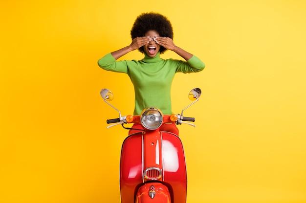 Фотопортрет женщины, закрывающей глаза на красном велосипеде с открытым ртом, изолирован на ярко-желтом фоне