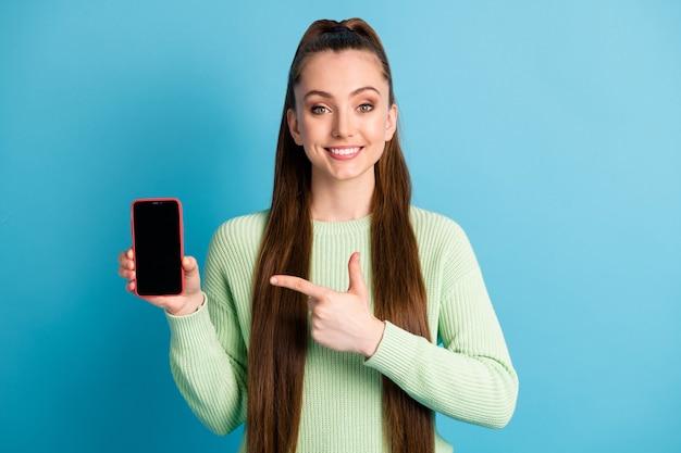 파스텔 블루 색상의 배경에 격리된 녹색 점퍼를 입은 빈 공간이 있는 전화를 가리키는 여성의 사진 초상화