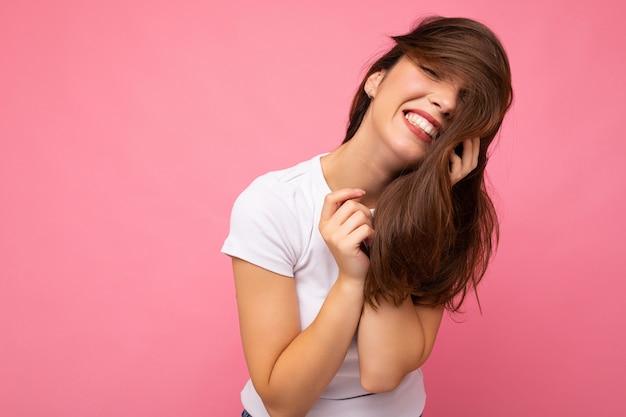 Фотопортрет молодой красивой улыбающейся хипстерской брюнетки в белой футболке с сексуальным макетом