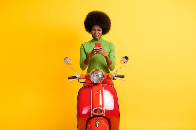 鮮やかな黄色の背景に分離されたsmsメッセージに嫌悪感を凝視して携帯電話を保持している赤いバイクのカジュアルな服装で若いブルネットのアフリカ系アメリカ人女性の写真の肖像画