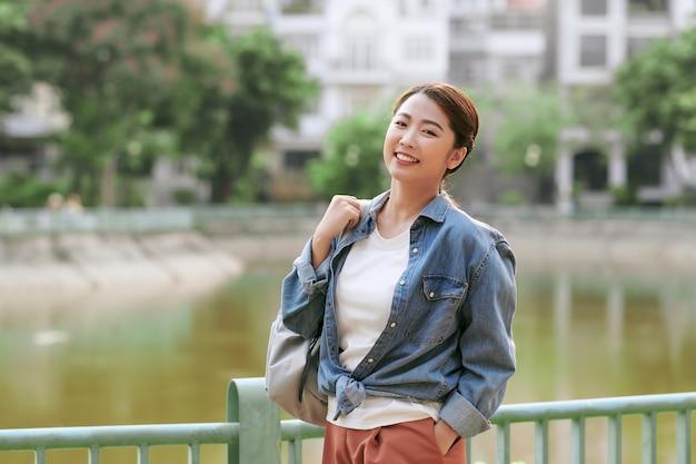 야외 포즈 회색 배낭을 들고 젊은 여자의 사진 초상화