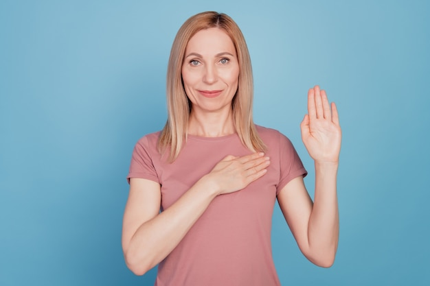 Photo portrait of serious young woman hand on chest promising tell truth isolated on blu color background