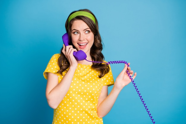 Photo portrait of woman holding wire of purple phone talking isolated on pastel light blue colored background