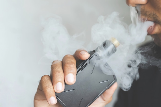 수염을 가진 사진 초상화 젊은 남자 보류 및 연기 확산의 흐름을 불고 그의 전자 담배 흡연.