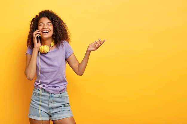Photo of positive african american girl talks on mobile phone, smiles broadly, raises hand, shares impressions about shopping, discusses last fashion trends