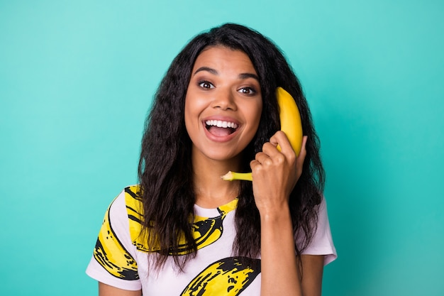 Photo of positive afro american girl call banana phone wear pink t-shirt isolated over teal color background