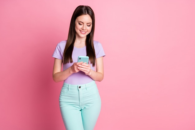 Photo of positive cheerful girl addicted social media user read smartphone news follow post comment wear turquoise trousers purple isolated over pastel color background