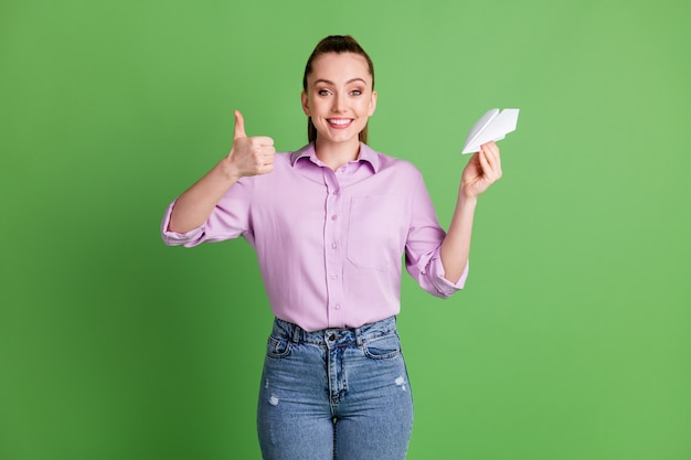 Photo of positive cheerful girl hold hand paper plane show thumb up sign wear lilac violet denim jeans isolated over green color background