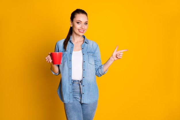 Photo of positive cheerful girl promoter hold cup with latte espresso point index finger copyspace indicate ads promotion wear stylish trendy outfit isolated bright shine color background