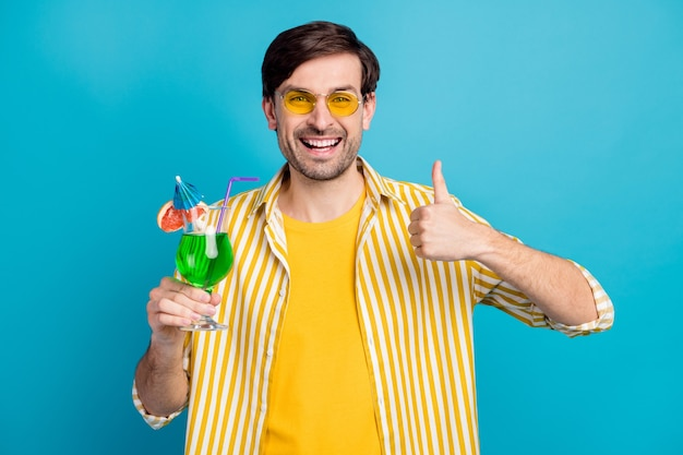 Photo positive cheerful guy traveler enjoy exotic trip hold glass cocktail approve beverage show thumbup sign wear striped white yellow shirt isolated over blue color background
