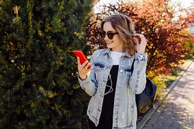 Photo of a positive cheerful teenage girl spends time in the park and using mobile phone.
