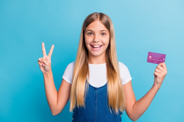 Photo of positive cute blond hair teen girl hold bank card show v-sign wear casual outfit isolated on pastel blue color background