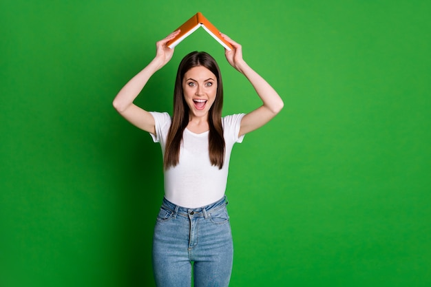 Photo of positive cute brunette hair young lady hold book above head wear white t-shirt denim jeans isolated on green color background