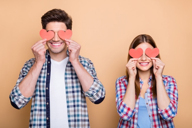 Photo of positive cute red redhair nice casual charming couple of two people holding valentine post cards with hands covering their eyes isolated over beige pastel color background