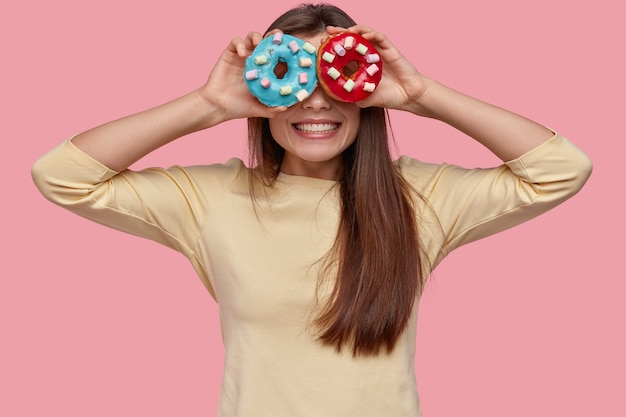 La foto della donna dai capelli scura positiva copre gli occhi con due ciambelle, ha un sorriso a trentadue denti, vestita con indifferenza