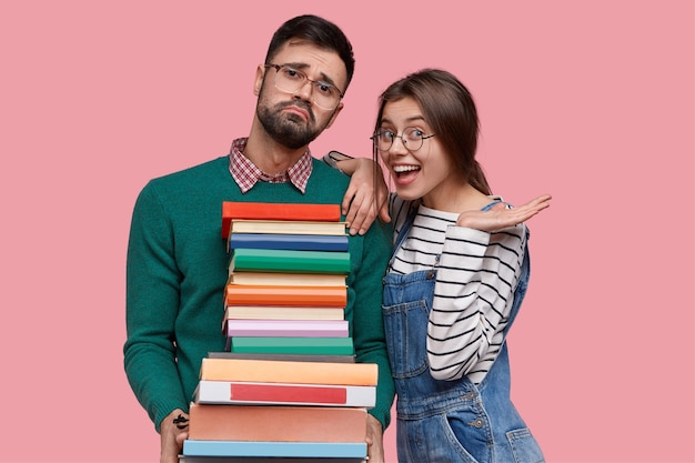 Photo of positive european woman wears striped sweater and overalls, leans at shoulder of tired male nerd with pile of thick books