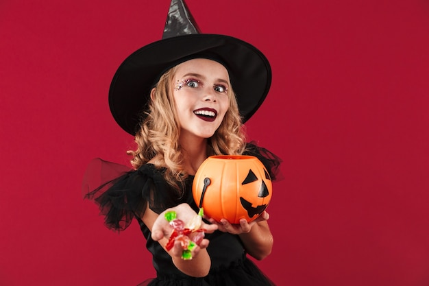 Photo of positive evil little girl witch in carnival halloween costume