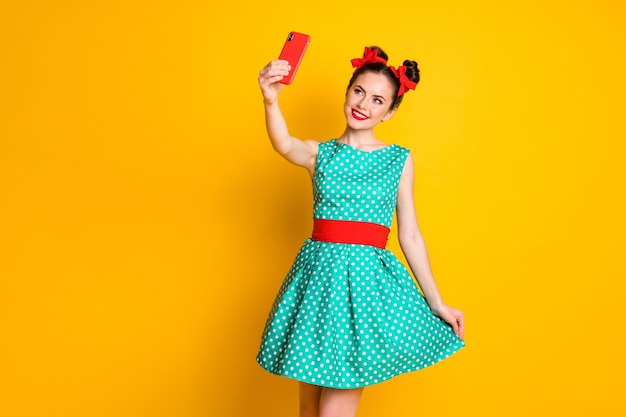 Photo of positive girl make selfie smartphone touch green skirt isolated over bright shine color background