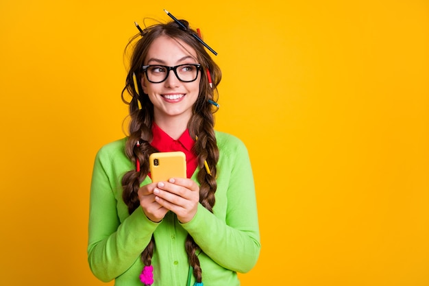 Photo of positive girl messy hairdo look copyspace use smartphone isolated over shine color background