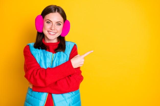 Фото позитивная девушка промоутер указывает пальцем copyspace указывает, что зима черная пятница рекламные объявления продвижение рекомендуют предлагать выбрать носить модный свитер изолированный яркий блеск цвет фона