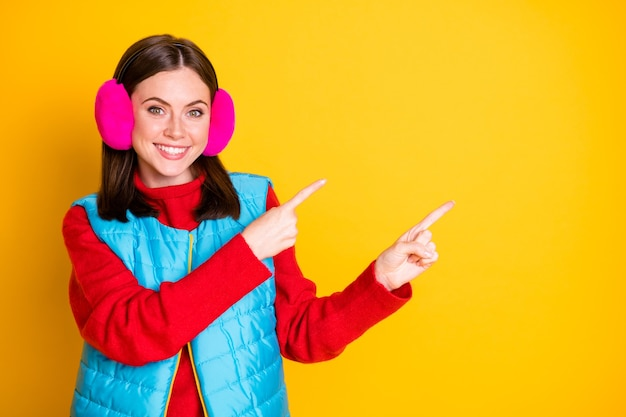 Фото позитивная девушка промоутер точка указательный палец copyspace продемонстрировать рекламу со скидкой продвижение настоящее обратная связь носить сезон розовая одежда изолированы яркий блеск цвет фона