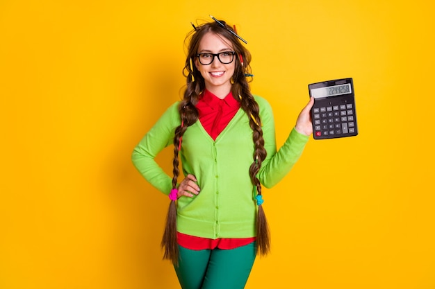 Photo of positive girl with pencil hairstyle hold calculator wear shirt pants isolated bright color background
