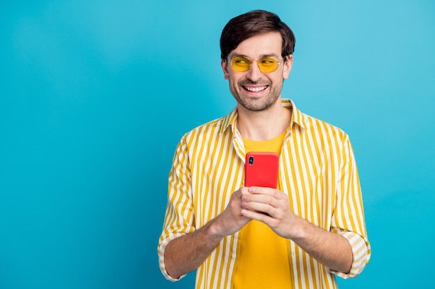 Photo of positive guy tourist use smartphone look copyspace enjoy social network blog instagram vacation post wear white style yellow clothes isolated blue color background
