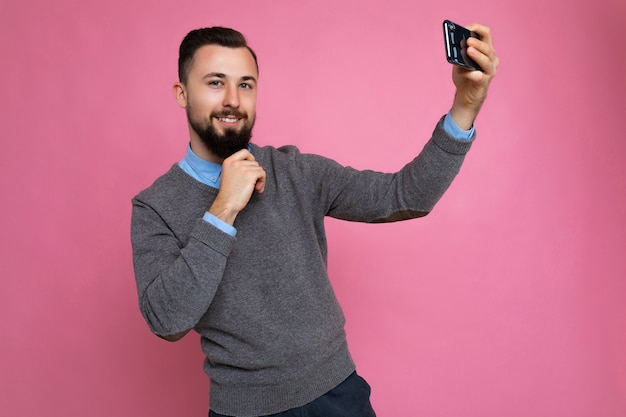Photo of positive handsome young brunette unshaven man with beard wearing casual grey sweater and blue shirt isolated on pink background wall holding smartphone taking selfie photo looking at camera.