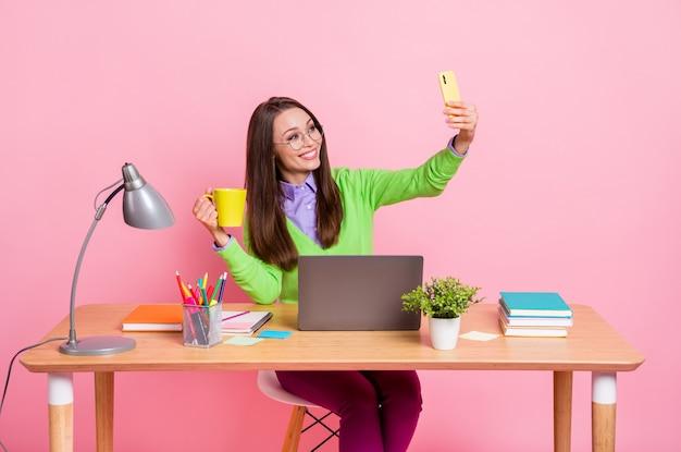 Photo of positive high school blogger girl sit table hold mug beverage make selfie smartphone isolated pink color background