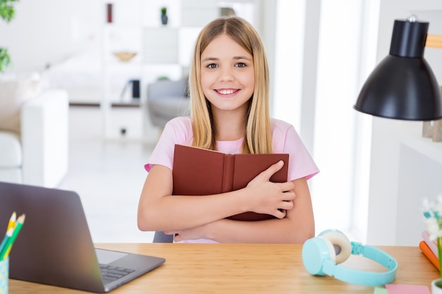 Photo of positive kid girl sit table desk read book enjoy interesting story hug embrace enjoy study fiction remote in house indoors