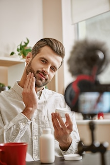 Photo of positive male beauty blogger applying cosmetic cream on his face while live streaming.