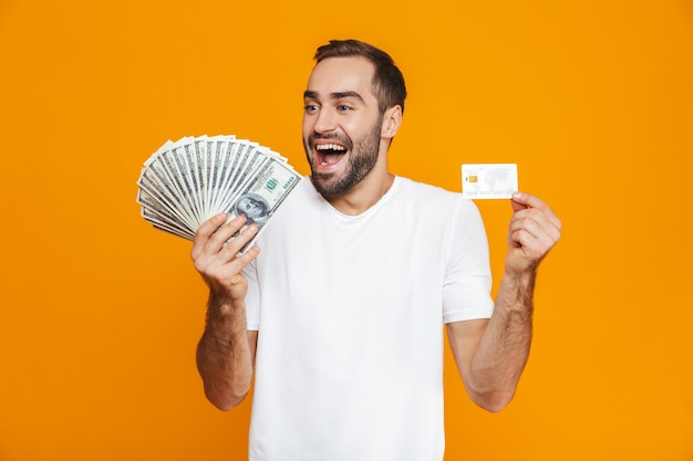 Photo of positive man 30s in casual wear holding bunch of money and credit card, isolated