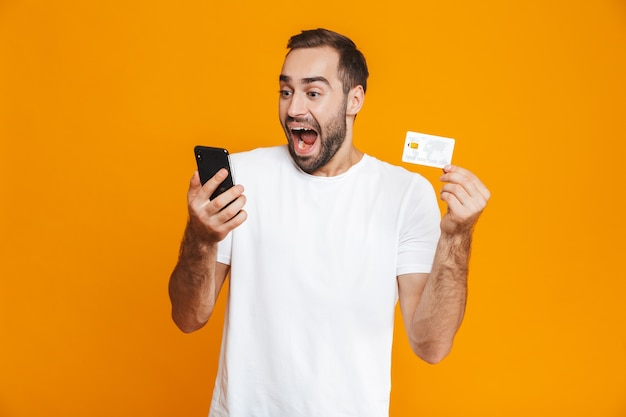 Photo of positive man 30s in casual wear holding smartphone and credit card, isolated