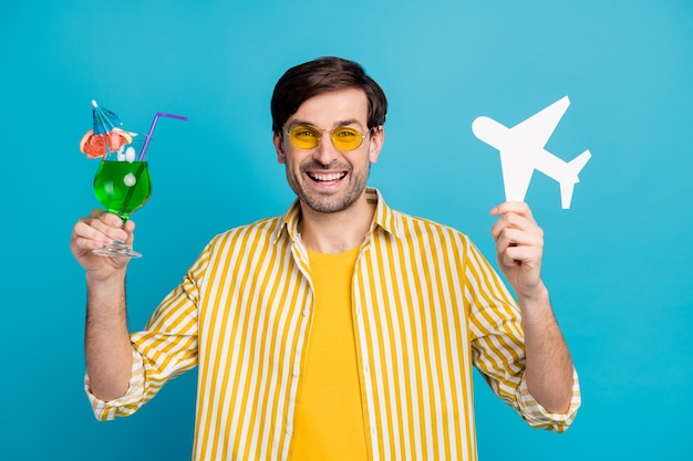 Photo of positive man traveler enjoy travel exotic trip hold alcohol beverage cocktail paper card plane wear yellow white striped shirt isolated over blue color background