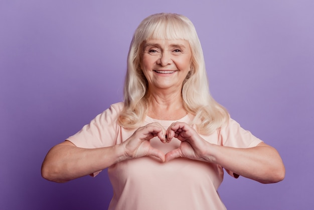 Photo of positive old wpman show heart gesture near chest on violet background