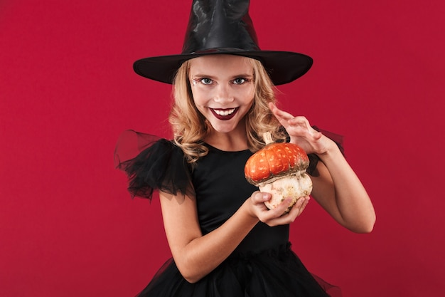 Photo of positive optimistic smiling little girl witch in carnival halloween costume