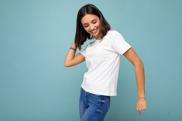 Photo of positive smiling joyful young beautiful brunette woman with sincere emotions wearing casual white t-shirt for mockup isolated over blue background with empty space and dancing.