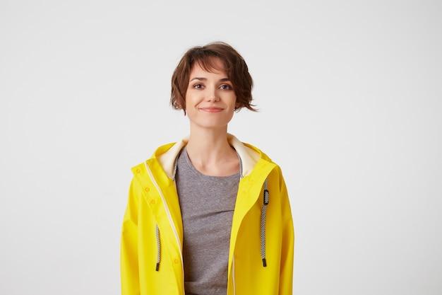Foto di positiva giovane bella donna in impermeabile giallo, godersi la vita, guarda la telecamera con espressioni felici, sorridendo sul muro bianco.