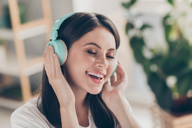 Photo of positive youth girl listen music on wireless blue headset wear casual style clothes in house indoors