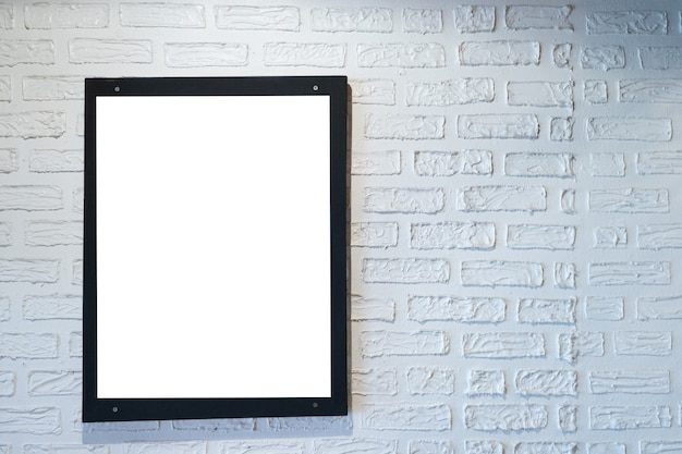 Photo of poster in a black frame on a white brick wall.